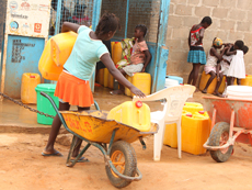 A child with a wheelbarrow at a water kiosk